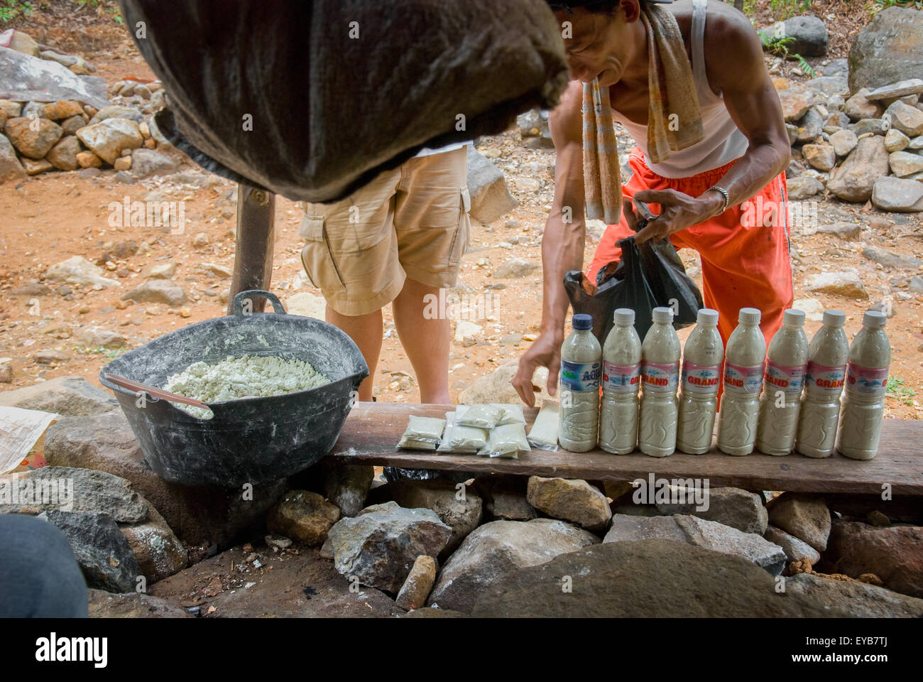 Man selling sulfur powders which are believed having curative effects to skin health. - Stock Image
