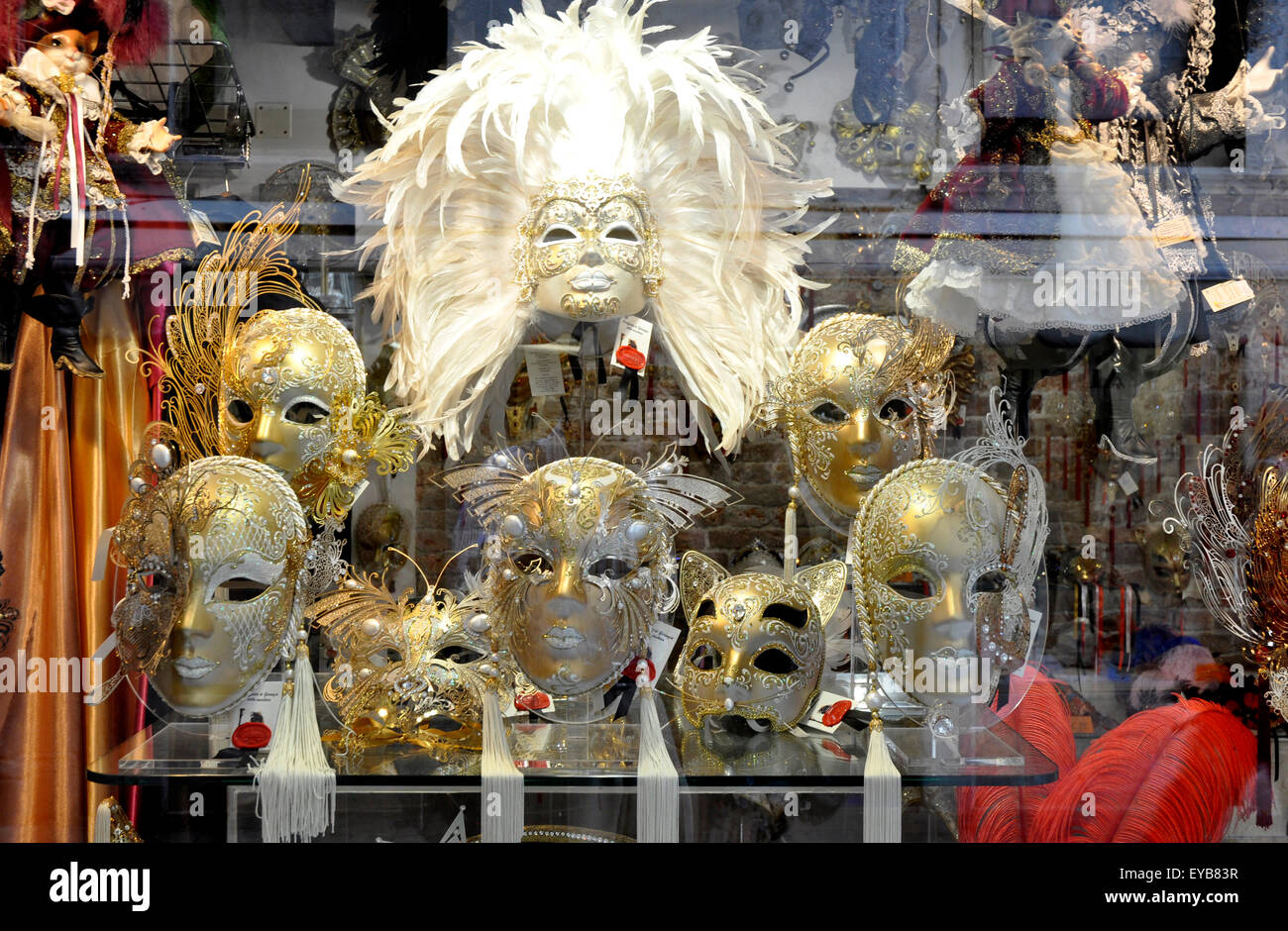 Venetian Carnival masks - mock gold - silver  feathers decorations - mystical - unreal  - window display - Venice - Stock Image