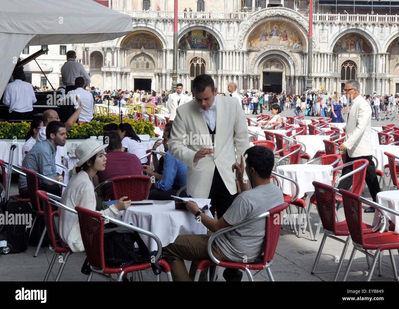Italy Venice Piazza San Marco cafe - customer and waiter - sign language - a misunderstanding perhaps - backdrop - Stock Image