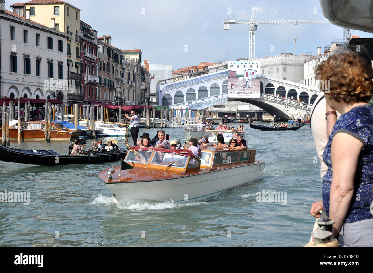 Italy -Venice - Canale Grande - gondolas water taxis busy scene backdrop Rialto bridge sunlight blue sky - Stock Image