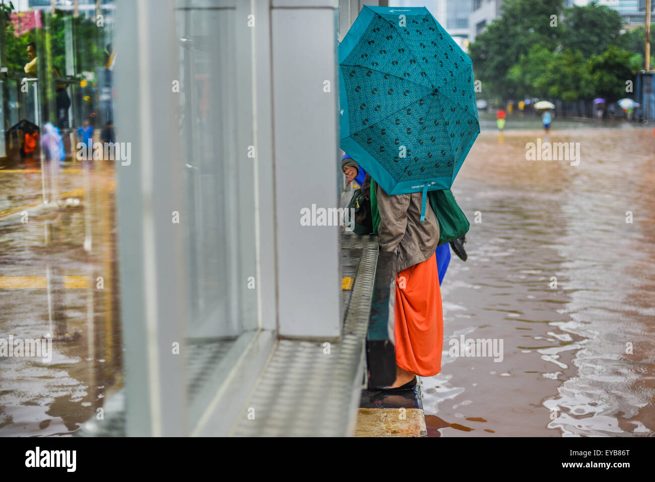 Women tries to avoid floodwater. Stock Photo