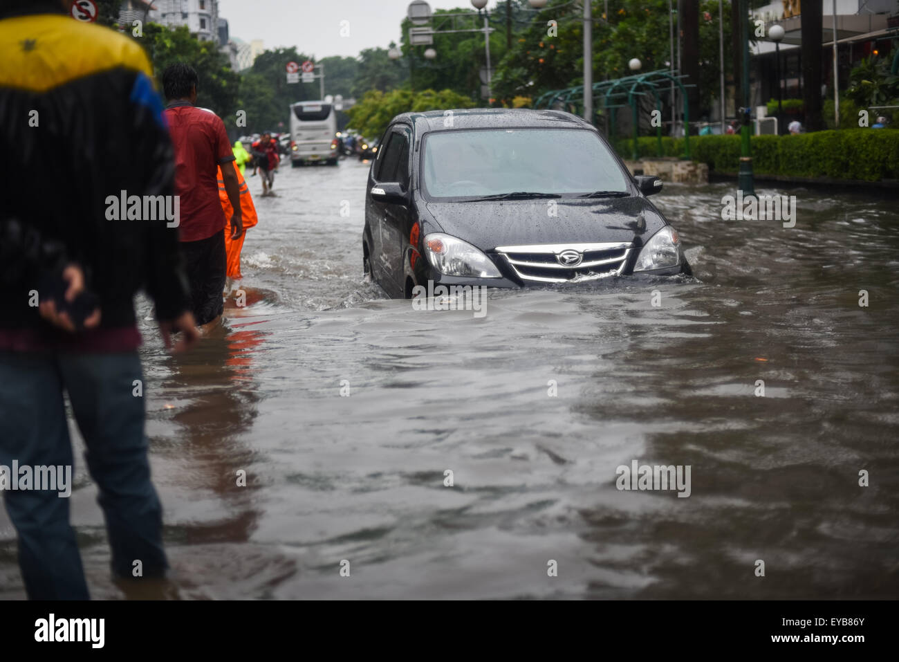 Car passing through flooded street. - Stock Image
