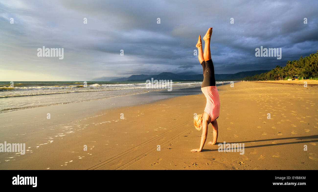 A young woman doing a handstand on beautiful tropical beach. - Stock Image