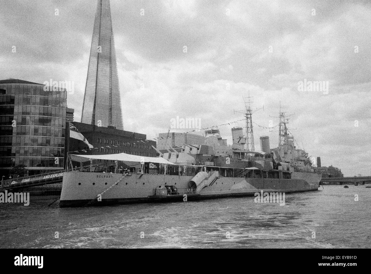 London tourist sights - HMS Belfast and the Shard seen from the river Thames, heavy grain from HP5 film - Stock Image