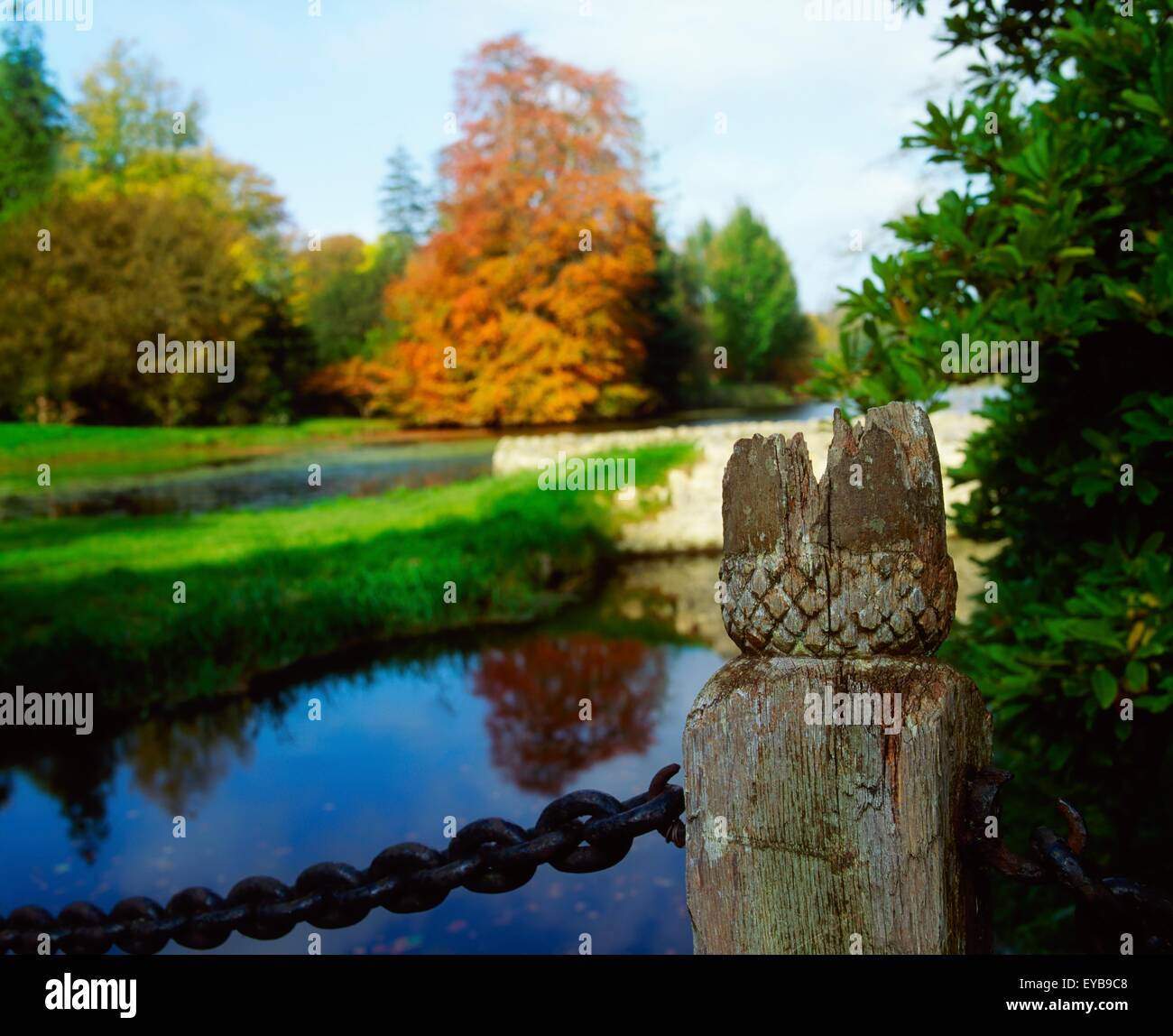 Birr Castle Demesne, Co Offaly, Ireland; Carved Post By The Lake During Autumn - Stock Image