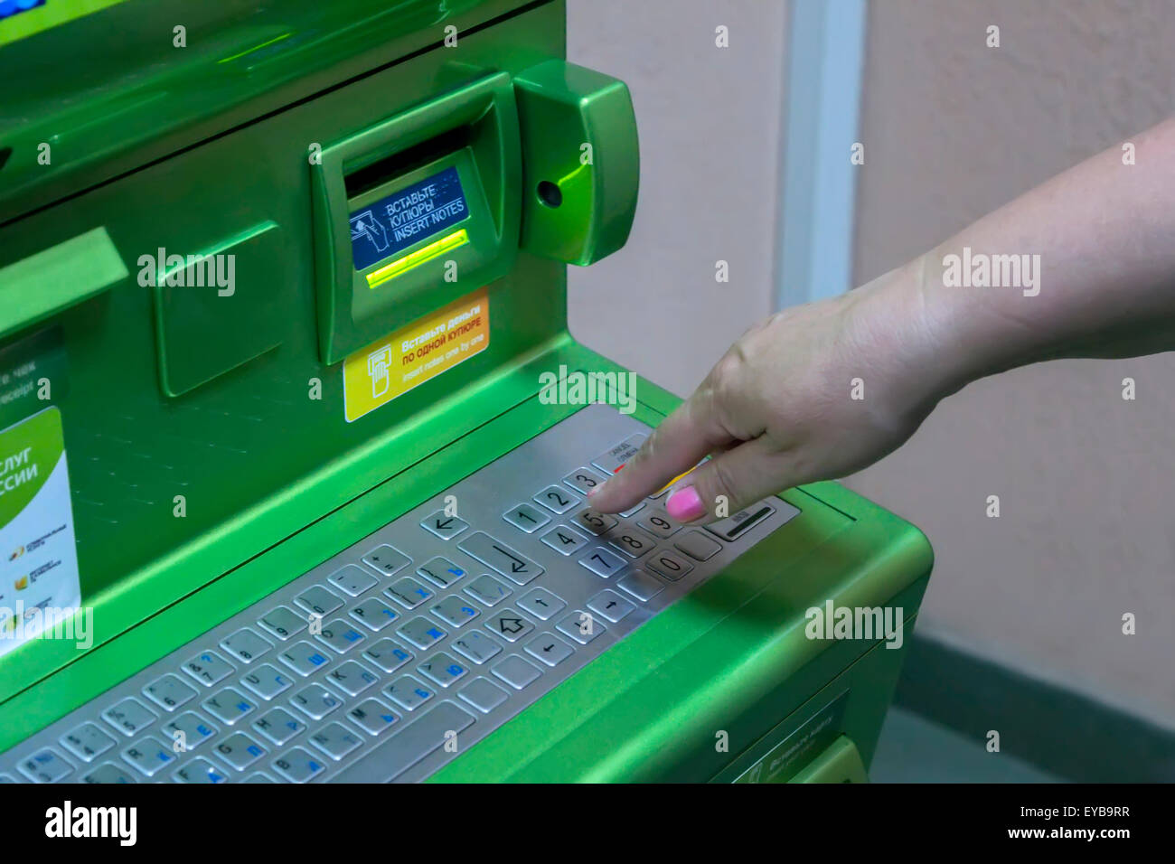 The hand of man (woman) is gaining PIN code on the keypad of the ATM terminal Stock Photo