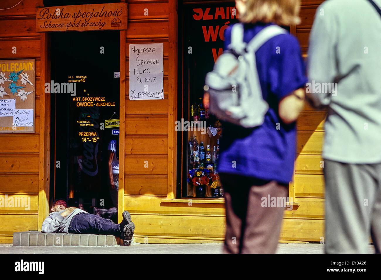 A man asleep in the doorway of a vodka store. Zakopane. Poland. - Stock Image