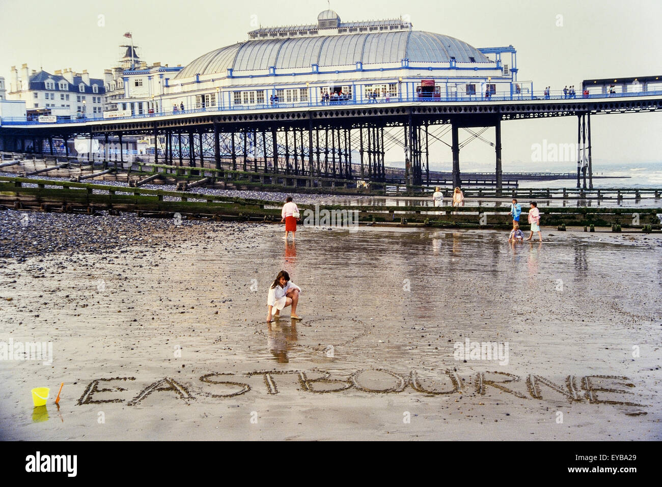 A young girl on Eastbourne beach after writing in the sand her love for the resort. East Sussex. England. UK - Stock Image