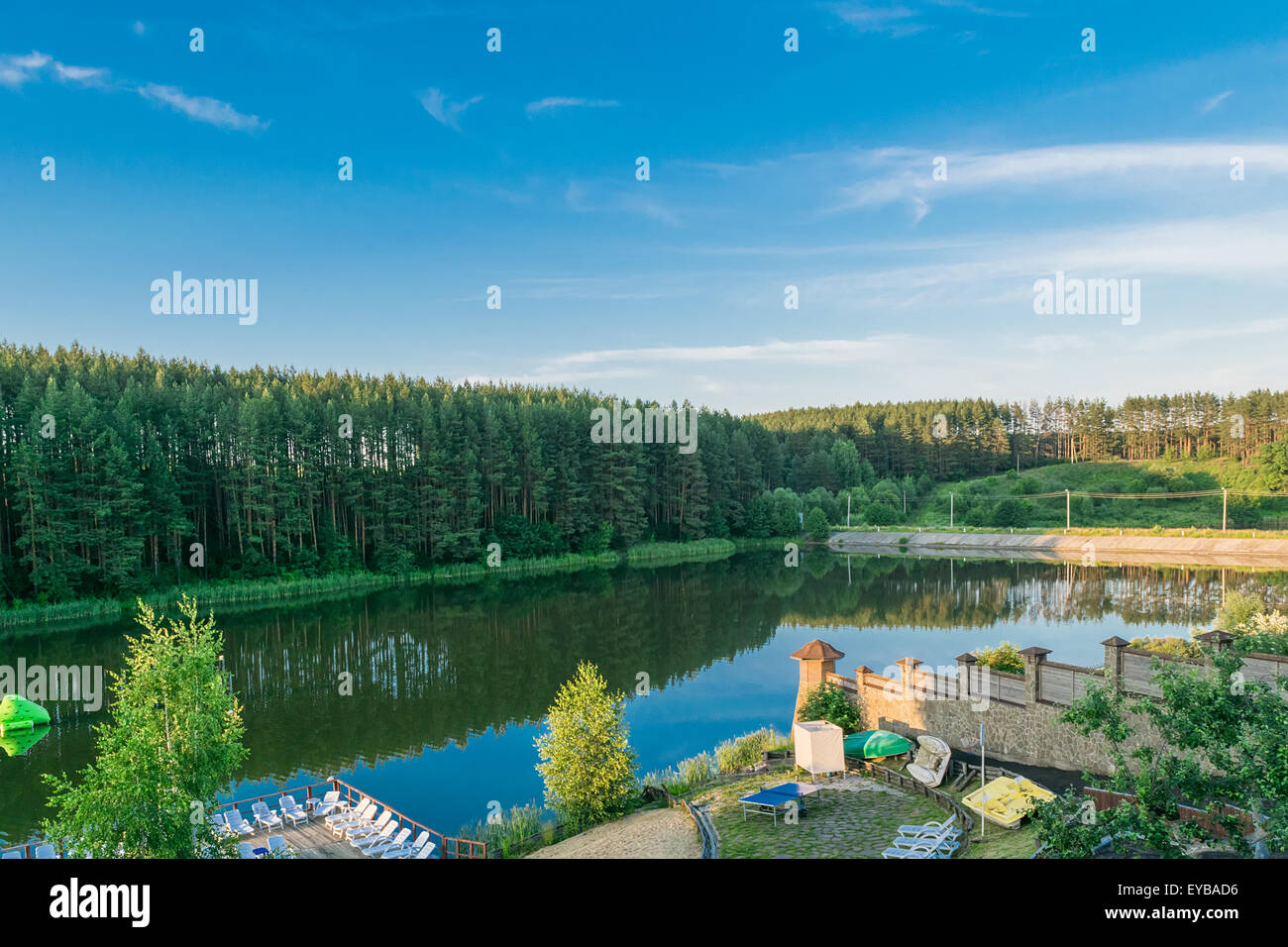Resting place on the beach on the shores of an artificial lake near the edge of the forest - Stock Image