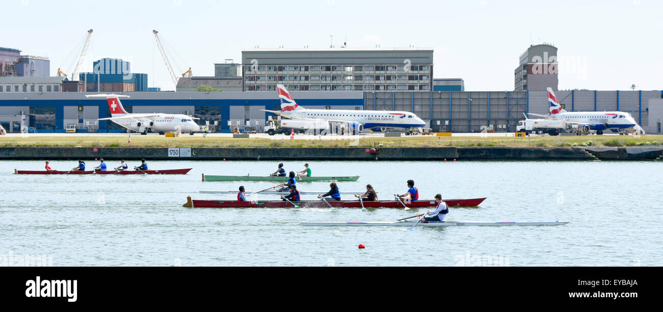 Aircraft at  London City Airport with rowers training in the old Royal Docks next to runway London Docklands Newham - Stock Image