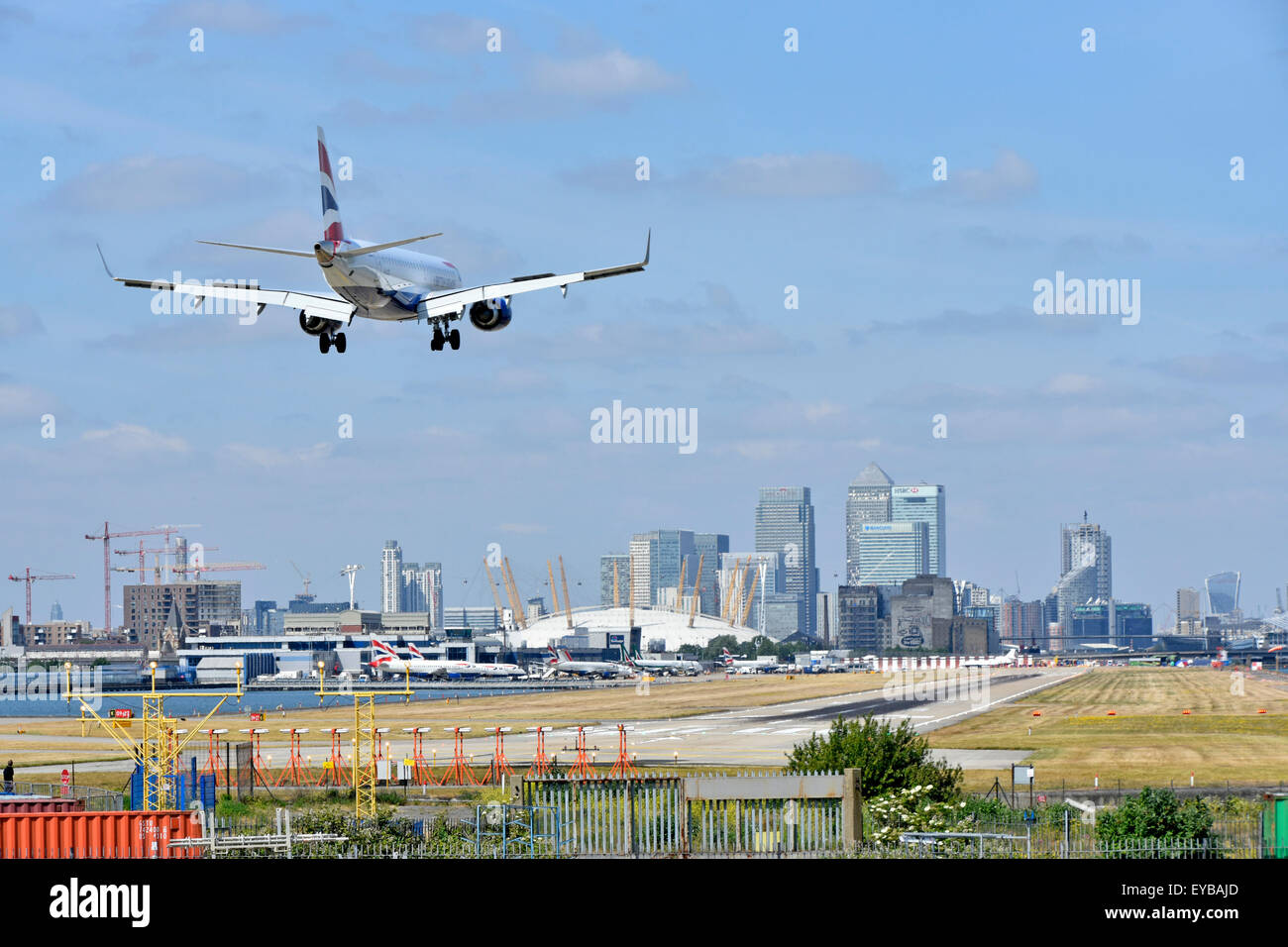 British Airways plane landing London City Airport Newham with O2 arena & Canary Wharf in London Docklands skyline - Stock Image