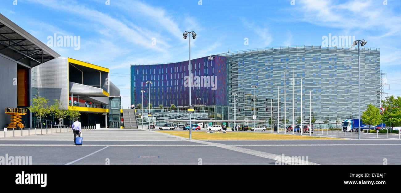Business man walking towards eastern entrance of London Excel exhibition centre yellow & adjacent Aloft W hotel - Stock Image