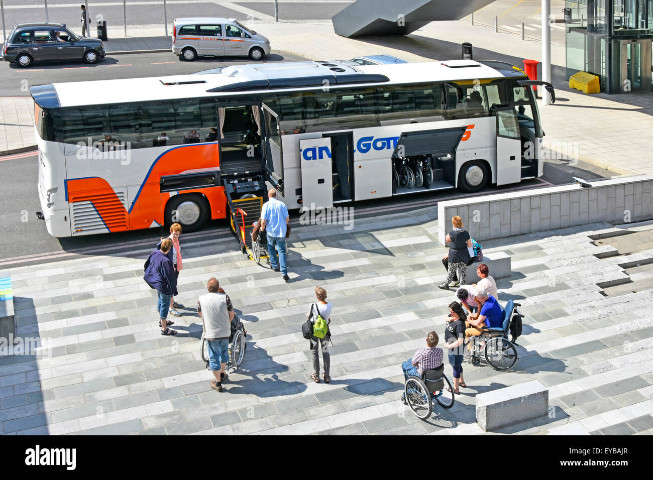 Wheelchair user passengers wait for platform elevator on coach bus adapted for disabled people to travel  ((see - Stock Image