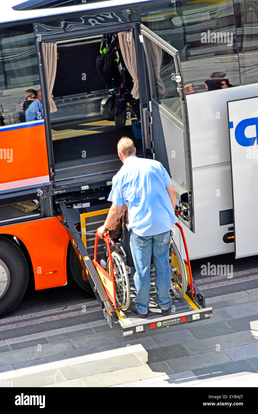 Wheelchair lift & man supervising disabled user enter coach interior from a hoist platform London England (see - Stock Image