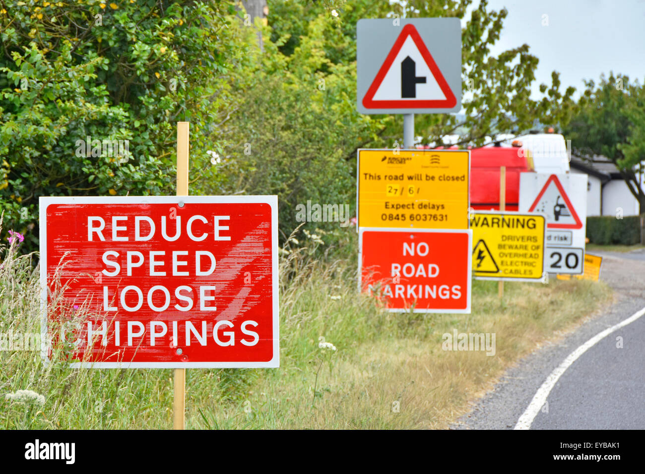 Road signs placed in long line to warn of top dressing gritting resurfacing works on a country lane in Essex England - Stock Image