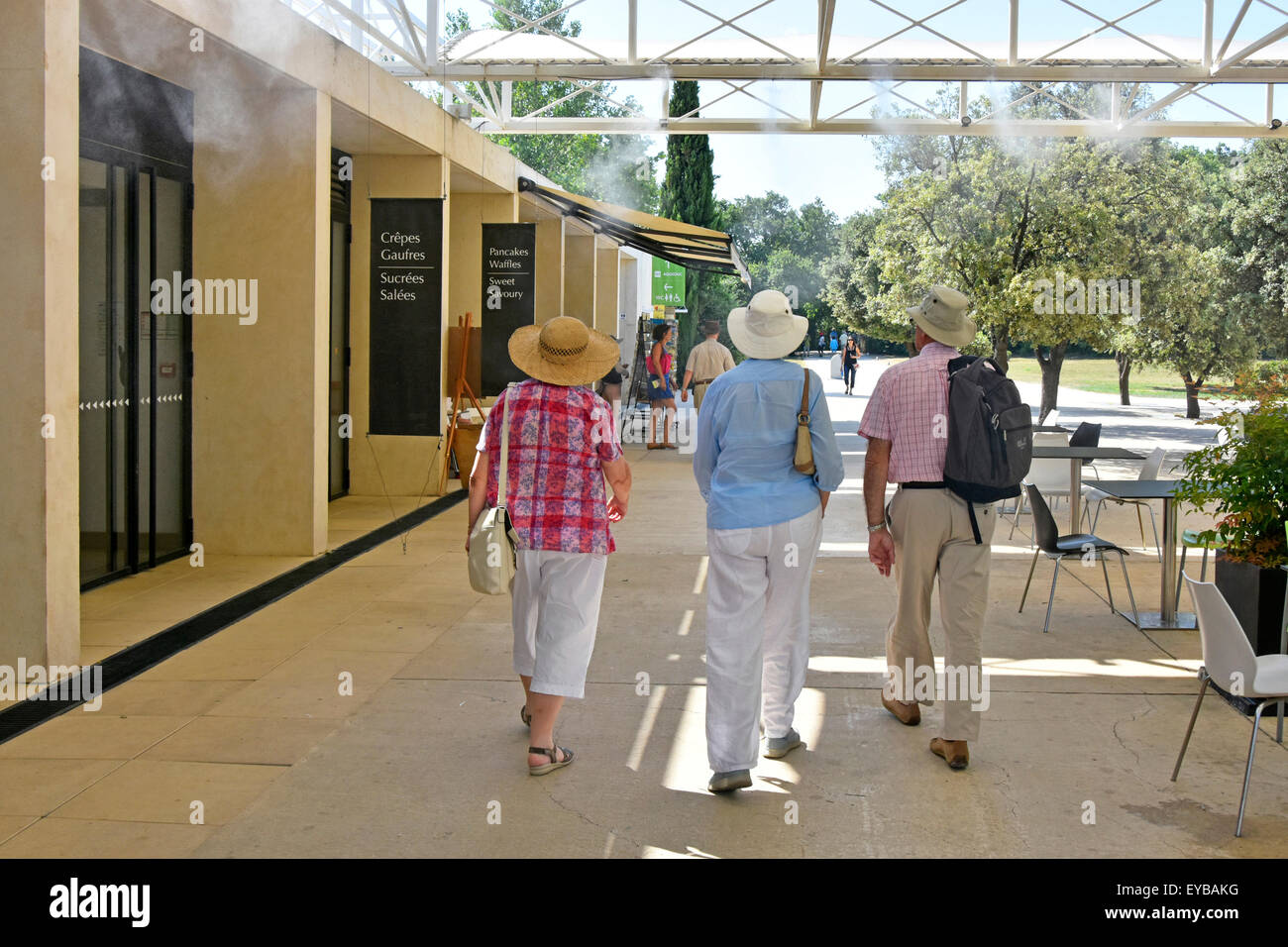 Tourists walk under mist or misting cooling system during heatwave through French Pont du Gard visitor centre towards - Stock Image