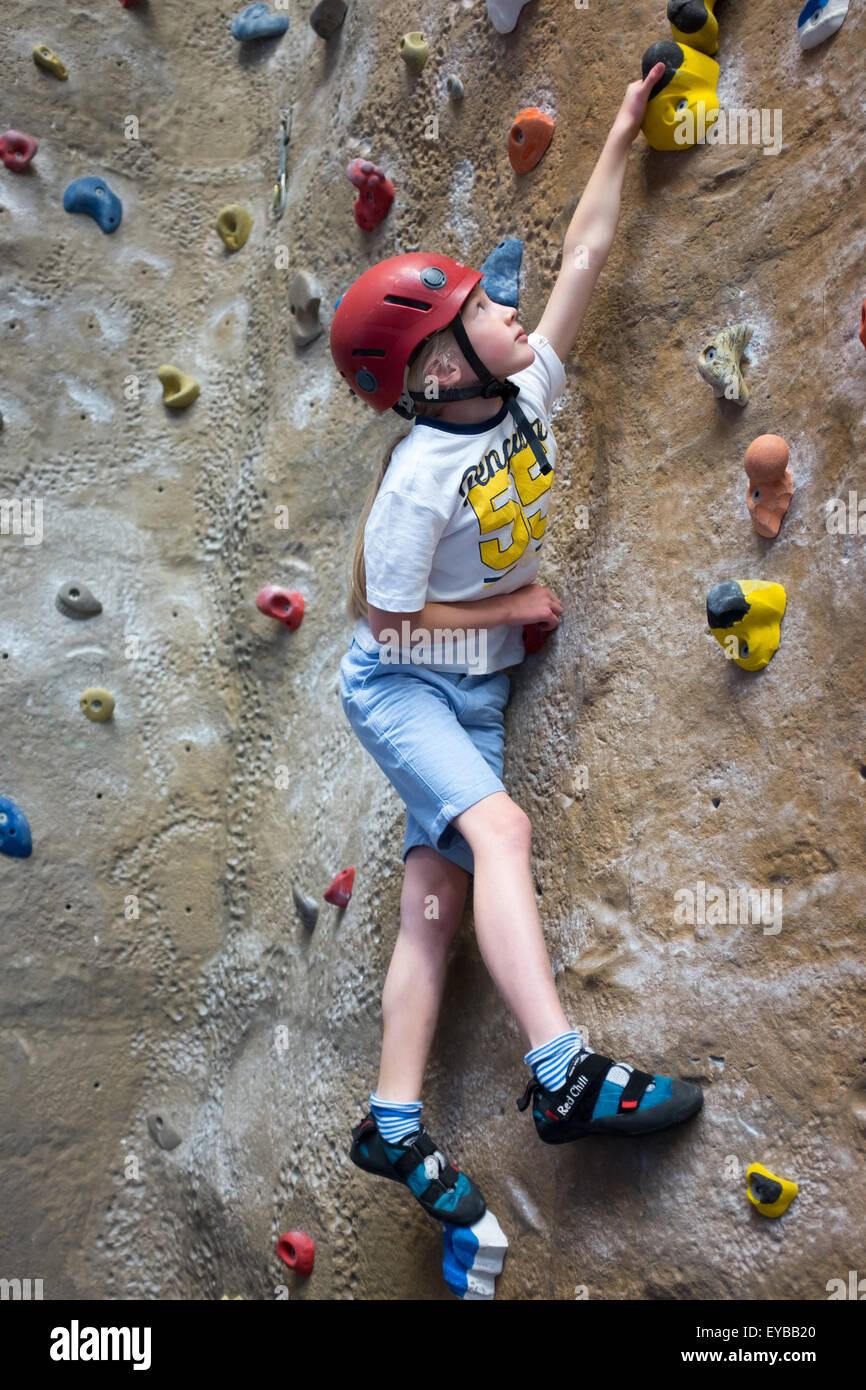 A young girl climbing at an indoor climbing centre wall - Stock Image