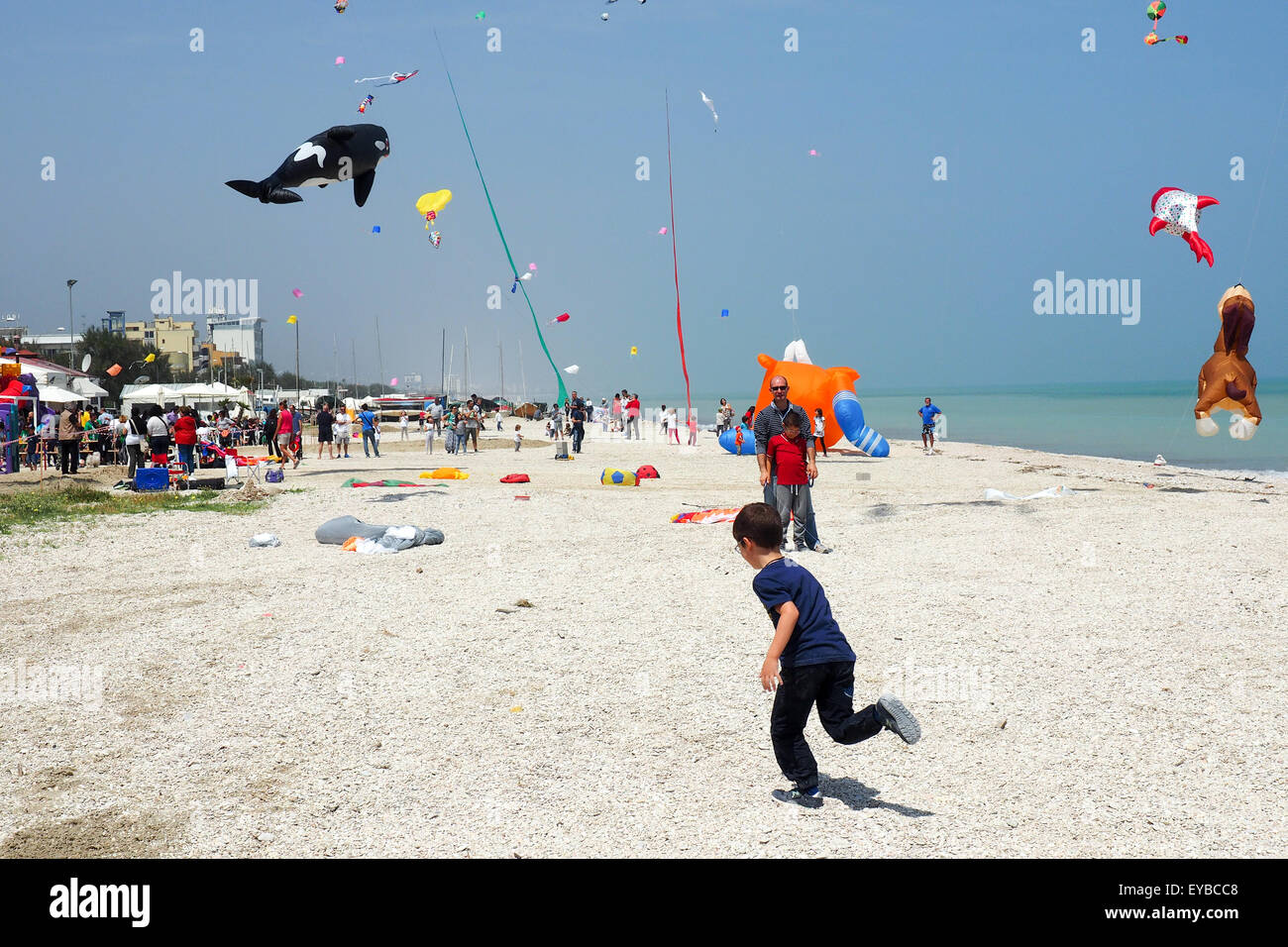 A young boy running on the beach, colourful and animal shaped kites flying over a beach. - Stock Image