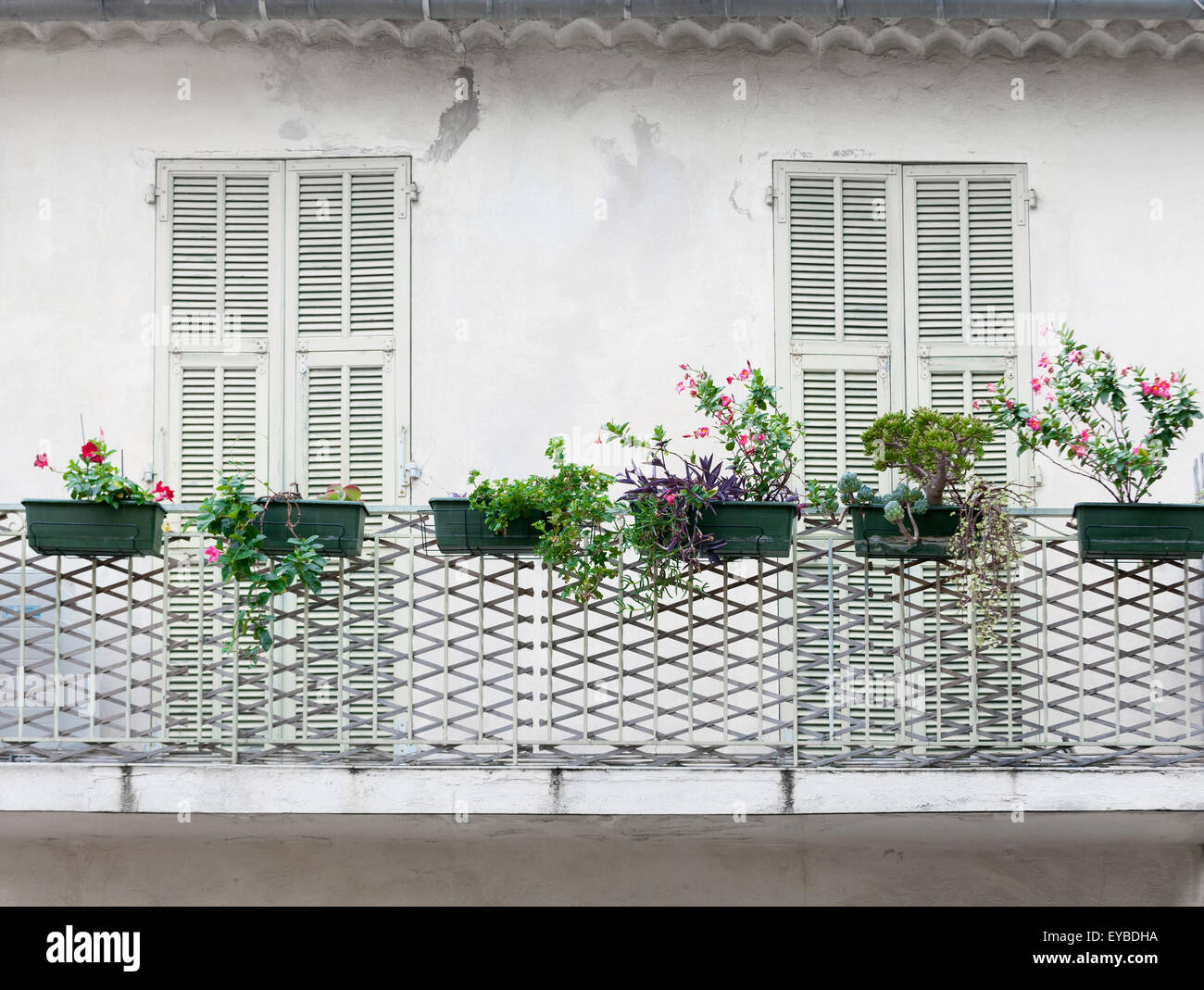 French balcony with closed doors and flower boxes on old house in Villefranche-sur-Mer, France. - Stock Image