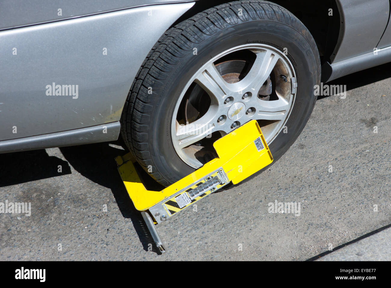 A Paylock tire boot immobilizes a car with outstanding parking violations in New York City. - Stock Image