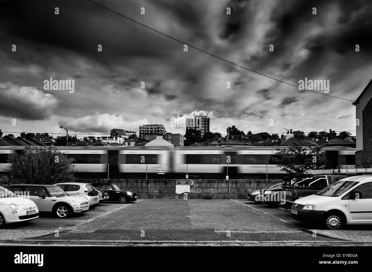 Monochrome Image of Train Speeding Through Old Leigh in Close Proximity to Houses - Stock Image