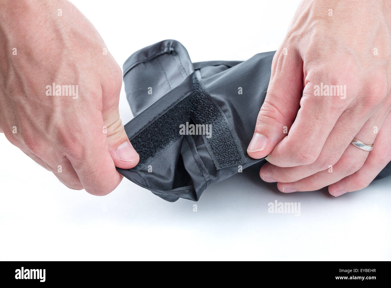 A close up shot of men's hands opening a black case closed with a velcro fastener on a white background. - Stock Image
