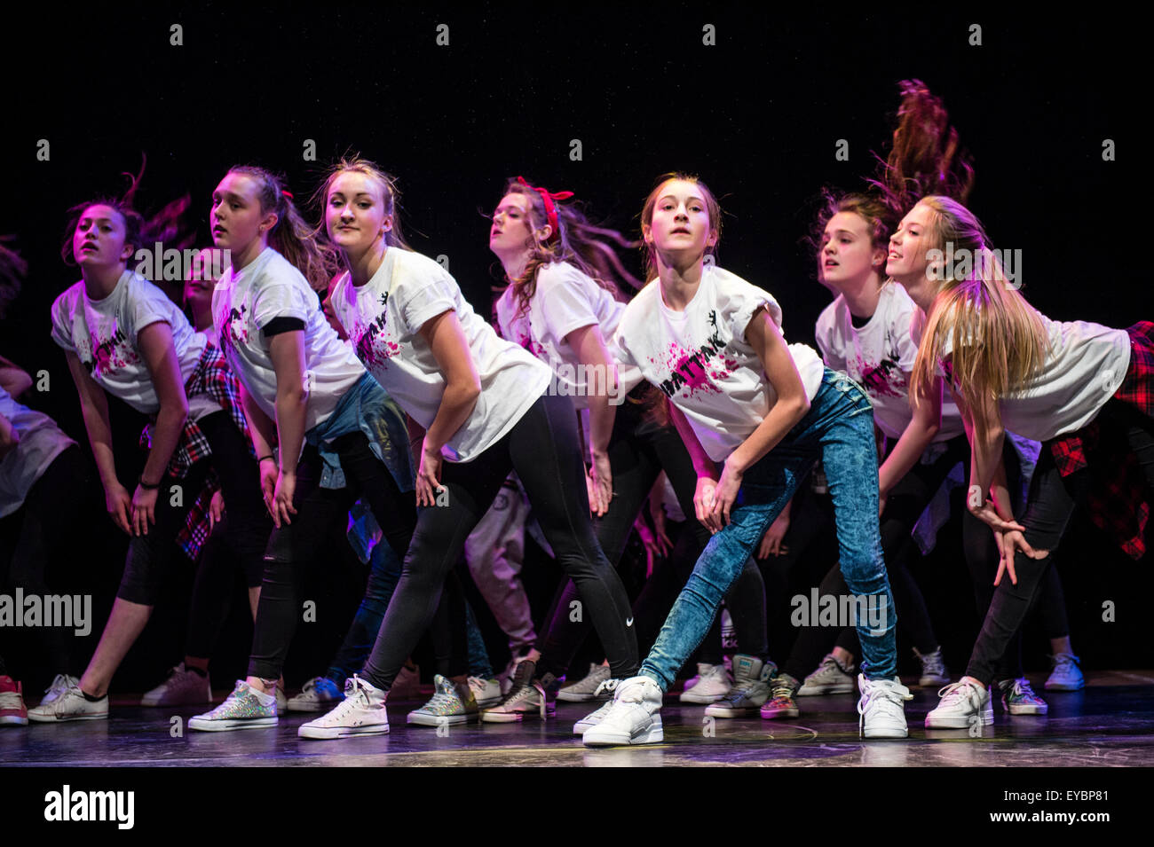 A group of teenage girls performing choreographed modern urban dance routines on stage at Aberystwyth Arets Centre - Stock Image