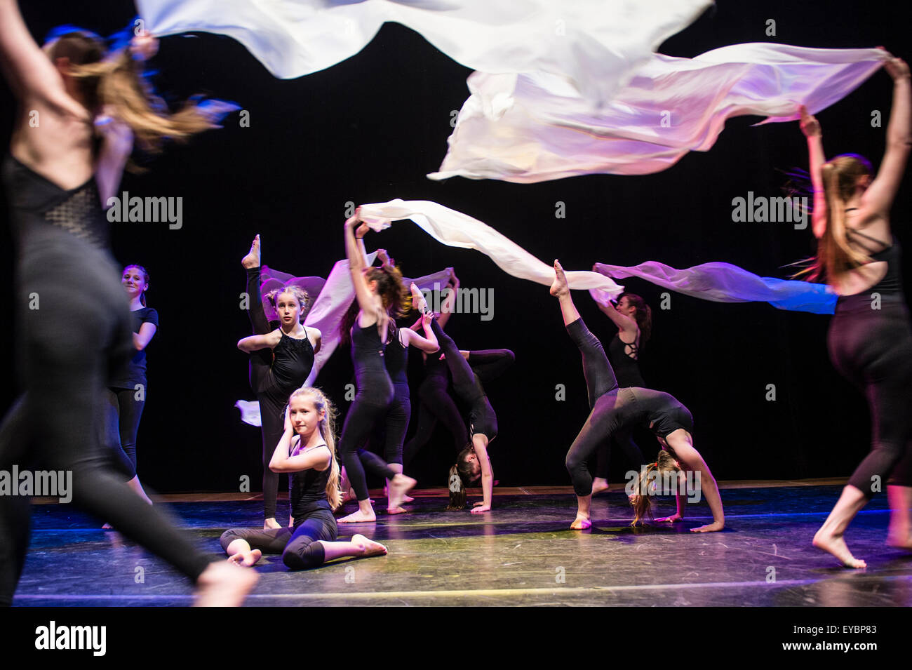 A group of teenage girls performing choreographed dance routines on stage at Aberystwyth Arets Centre Wales UK - Stock Image