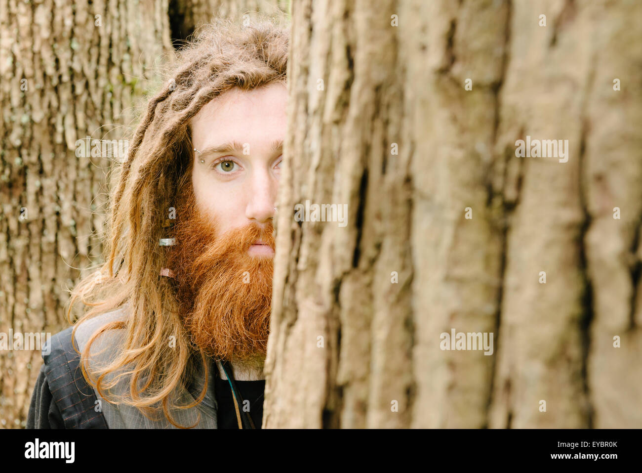 A hippy man with dreads in the forest - Stock Image
