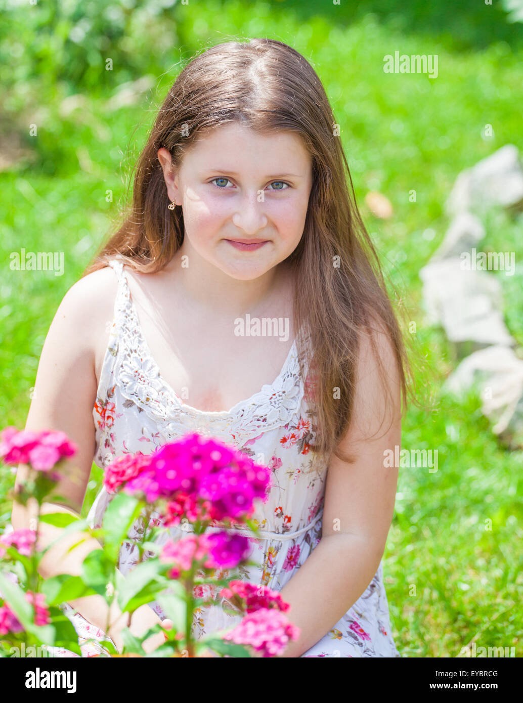Portrait of a 10 year old girl enjoying the flower garden at home ...