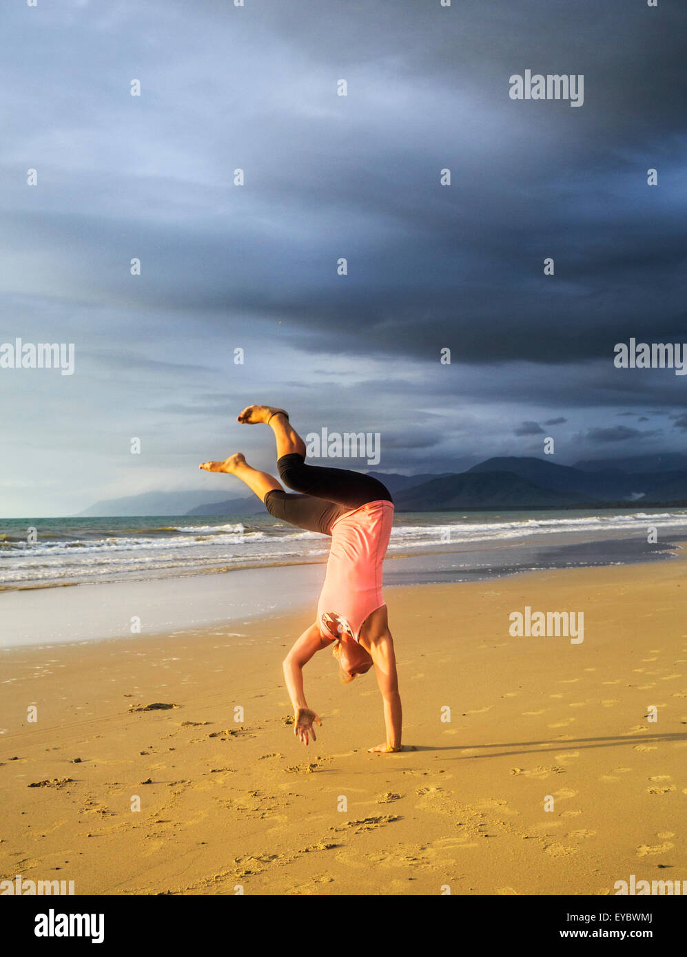 A young woman doing a cartwheel on the beach. - Stock Image