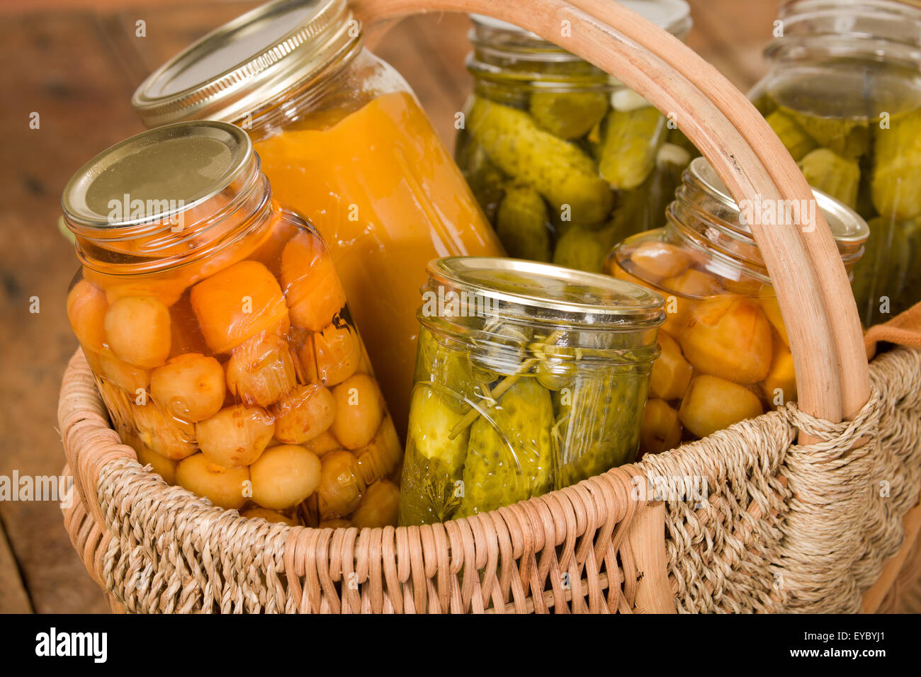 Home-canned produce (Rainier cherries, butternut squash soup and dill pickles) in a large wicker basket on a rustic - Stock Image