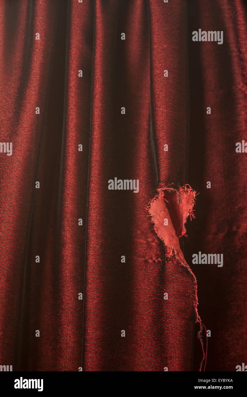 Luxurious, burgundy velvet fabric with a tear in it.  Could represent a torn drapery or dress. - Stock Image