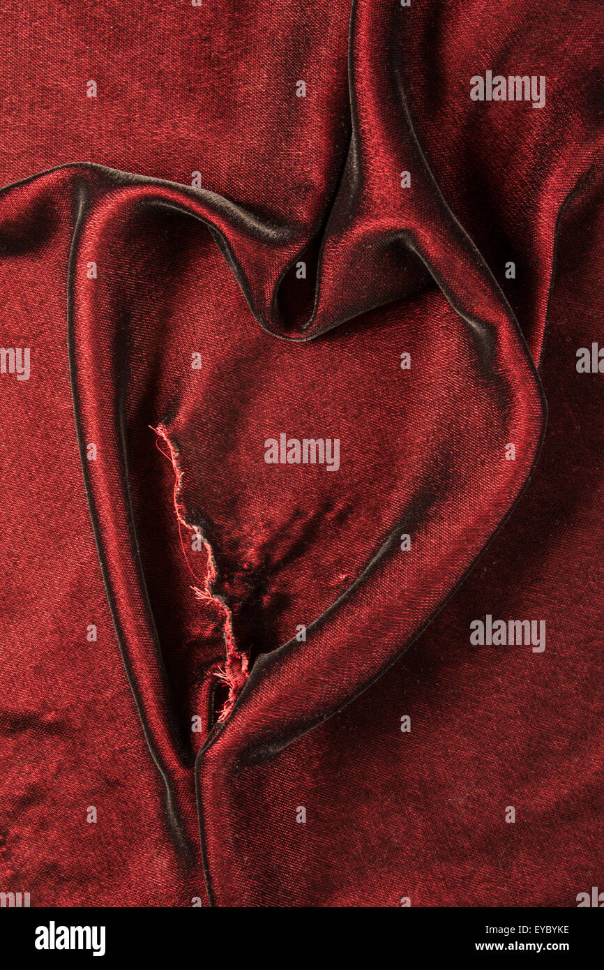 Burgundy velvet fabric with a tear in it, pulled into a heart shape - Stock Image