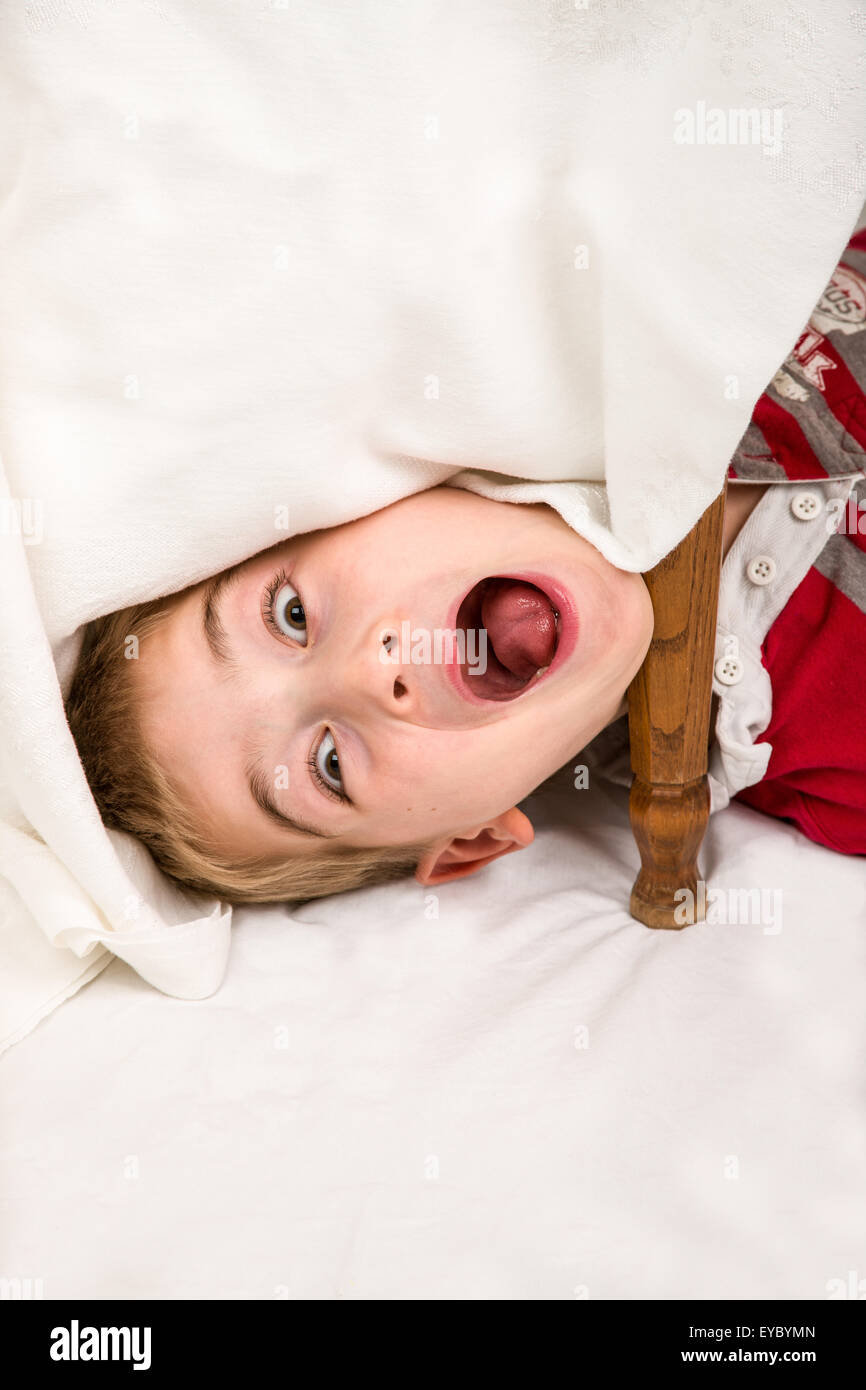 Six year old boy having fun making faces under a covered table - Stock Image
