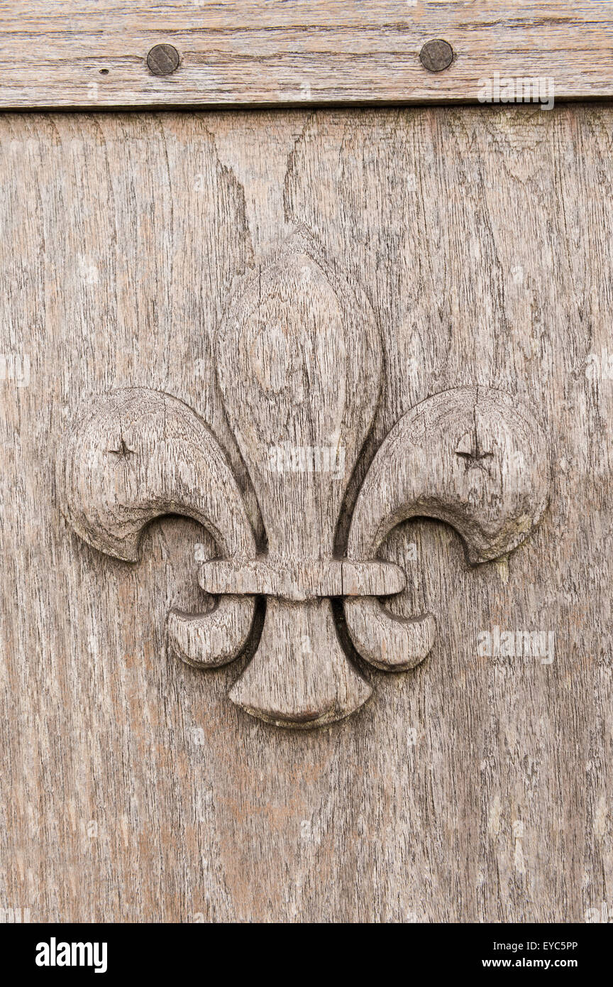 Scout emblem carved into an oak bench as decorative reminder and symbol for services rendered weathered and sun - Stock Image