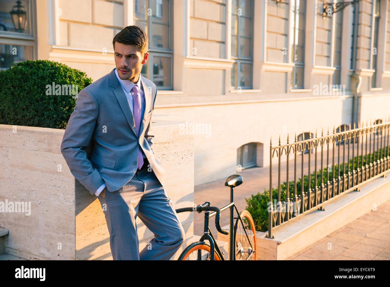 Handsome businessman standing outdoors in town - Stock Image
