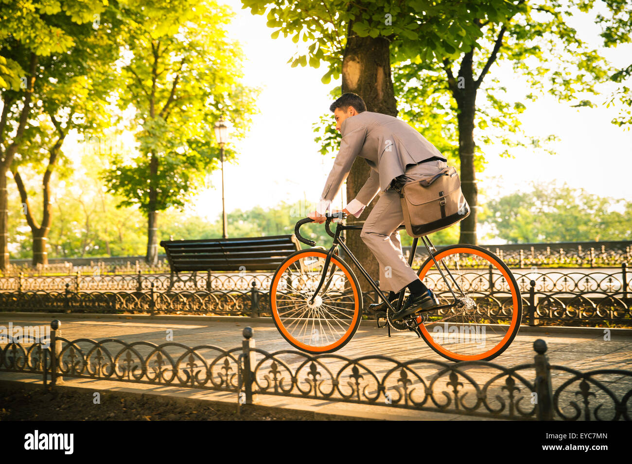 Businessman riding bicycle to work in park - Stock Image