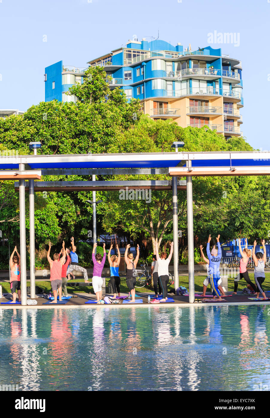 A mixed group of men and women in a yoga class beside an outdoor swimming pool in Cairns, Australia - Stock Image