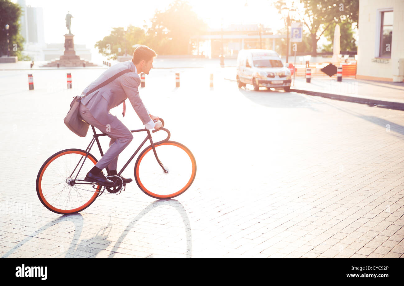 Businessman riding bicycle to work in town - Stock Image