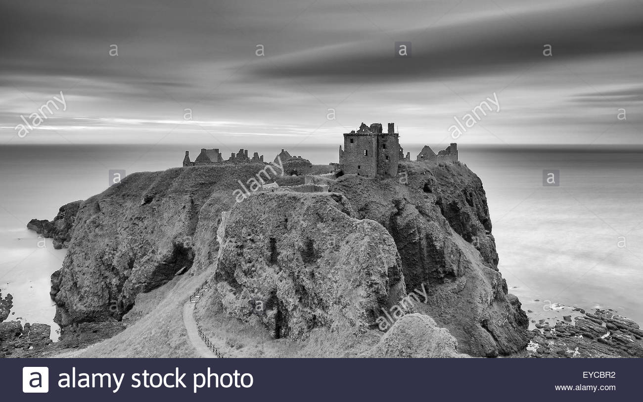A long exposure black and white photograph of Dunnottar Castle at Sunrise. - Stock Image