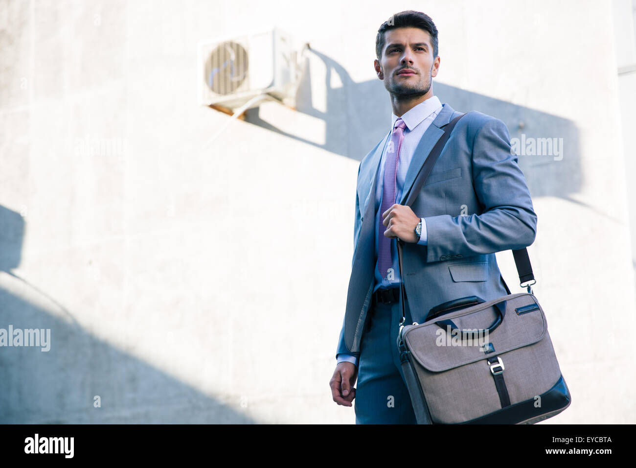 Portrait of a confident businessman standing outdoors near office building - Stock Image