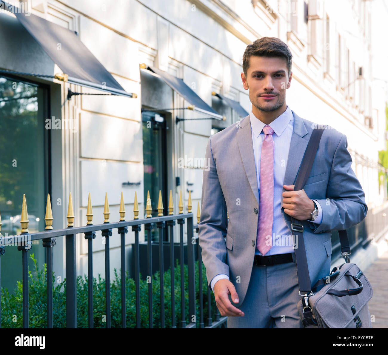 Portrait of a handsome young businessman walking in the city - Stock Image