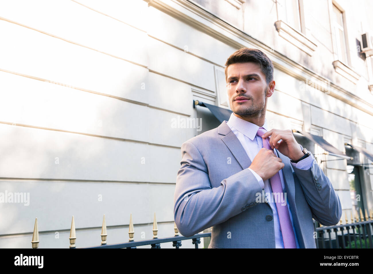 Handsome businessman straightens his tie outdoors - Stock Image