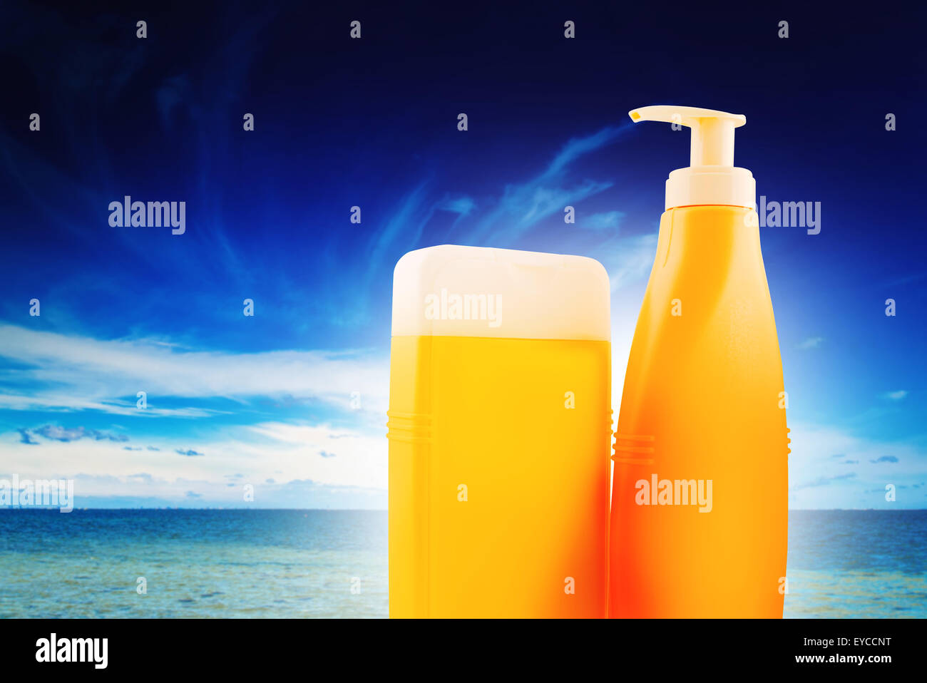 Blank Suntan Lotion Bottles on Sunny Seaside Beach - Stock Image