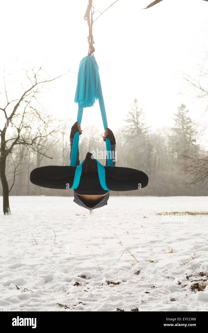 Young woman practicing aerial yoga outdoors - Stock Image