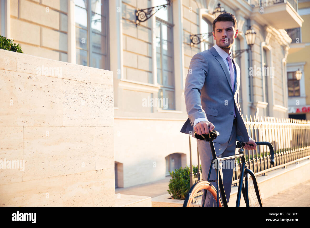 Portrait of a confident businessman standing with bicycle in old town and looking away - Stock Image