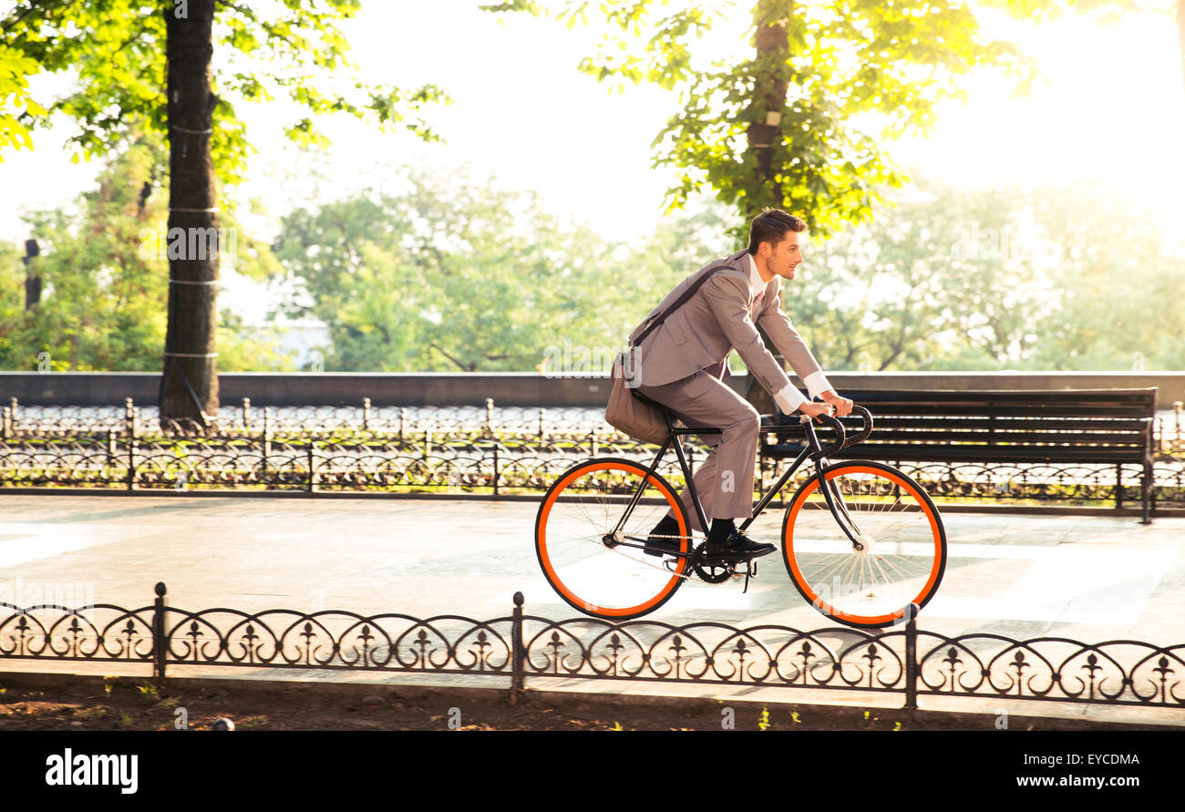Handsome businessman riding bicycle to work in park - Stock Image