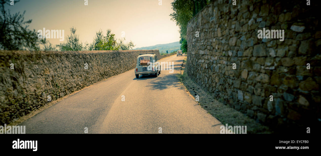 Classic Fiat 500 car driving on a road in Florence, Italy. Shot from behind. - Stock Image