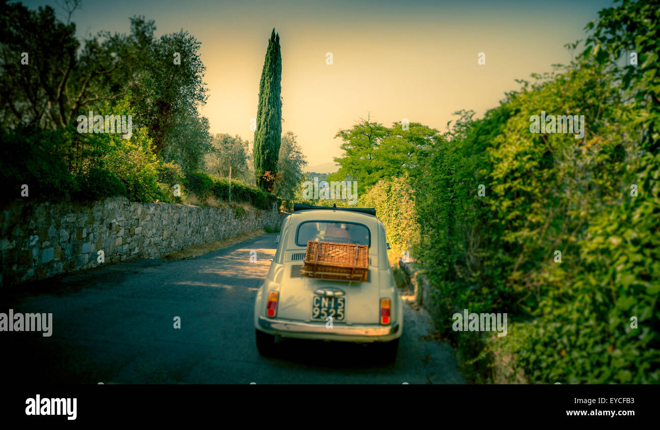 Classic Fiat 500 cars driving on a road in Florence, Italy. Shot from behind. - Stock Image